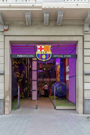 The official FC Barcelona Store shines in club colors of the Spanish soccer team, near Jardins de la Reina Victòria in Spain
