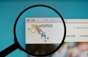 The Official Site of The Bahamas on a computer screen with a magnifying glass