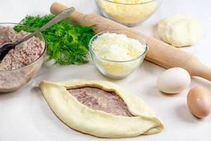 The process of making Adjarian khachapuri with raw ingredients