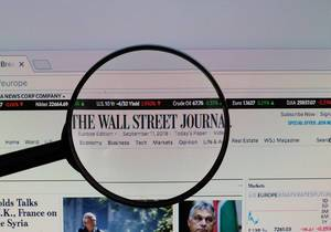 The Wall Street Journal Logo am PC-Monitor, durch eine Lupe fotografiert