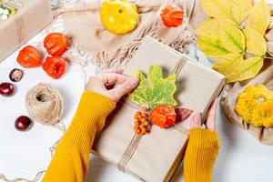 The woman wraps a gift at thanksgiving on autumn background (Flip 2019)
