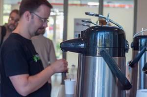 Thermoskannen mit Kaffee und Tee und Teilnehmer mit Bechern im verschwommenen Hintergrund