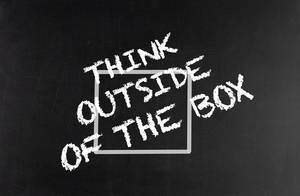 Think outside of the box text on blackboard