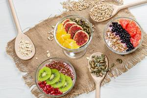 Three bowls of oatmeal with fresh fruit and seeds on a burlap background with wooden spoons (Flip 2019)