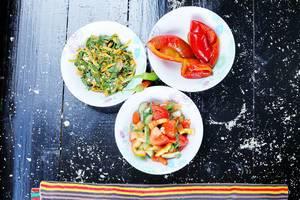 Three bowls of salad: pickled peppers, fresh vegetables and carrots salad. Black background (Flip 2019)