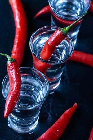Three glasses full of vodka and hot pepper