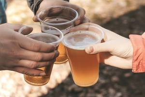 Three hands holding plastic beer glasses on spring nature background