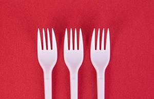 Three plastic forks on red background