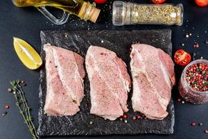 Three raw steaks with ingredients on a black background, top view