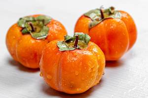Three ripe orange persimmons on a white wooden background
