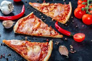 Three slices of pizza with bacon and tomato sauce with spices on a black background
