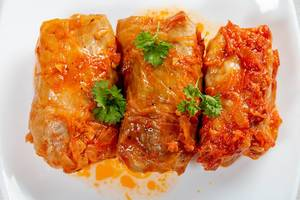 Three stuffed cabbage rolls in tomato sauce on a white plate (Flip 2019)