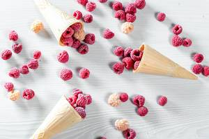 Three waffle cones with red and yellow raspberry on white wooden background