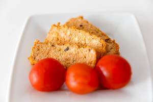 "Three washed tomatoes on a white plate, in front of the Mediterranean organic meat substitute ""Tofu Rosso"" by Taifun"
