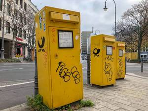 Three yellow mailboxes of the German post painted with graffiti at intersection