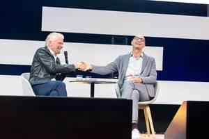 Tim Höttges und Richard Branson geben sich die Hand und Lachen dabei