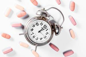 TIme for taking medication: pills and an alarmclock