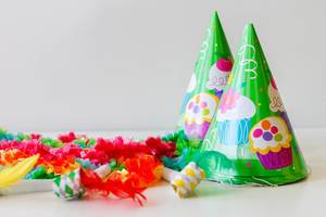 Time to party: green cone hats, whistles and garlands on a white background