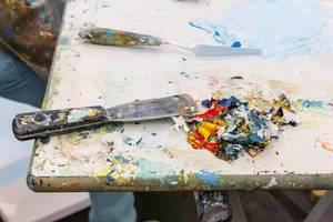 Tisch eines Künstlers mit Farbflecken, Spachtel und Farbresten