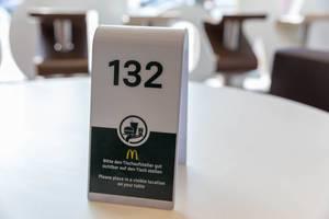 Tischaufsteller bei McDonalds wird als Platzhalter für die Essensbestellung auf dem weißen Tisch aufgestellt