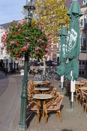 Tische und Stühle eines Cafes mit Sonnenschirmen und einer Blume an einem Laternenmast in Venlo