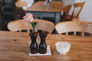 Tischutensilien in einem Restaurant. Rose in einer Vase, Zuckerdose, Salzmühle und Pfeffermühle