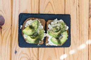 Toastbrot mit Ricotta und Avocado mit Steinplatte auf Holztisch