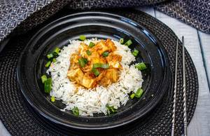 Tofu in Erdnusssauce in schwarzem Teller
