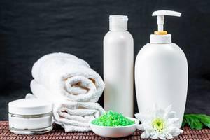 Toiletries in white with green bath salts on dark background