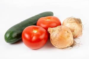 Tomaten, Gurke und zwei Zwiebeln mit Schale vor weißem Hintergrund