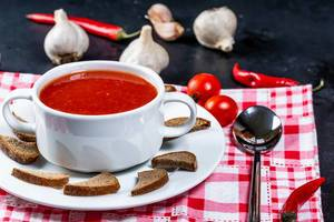 Tomatensuppe in einer Terrine mit Croutons, Knoblauch, Chili und einem Löffel auf dem roten Abtrockentuch, auf dem schwarzen Tisch