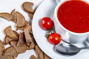 Tomatensuppe in einer Terrine mit frischen Cocktailtomaten und Schwarzbrot