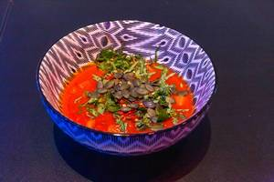 Tomato, carrot and celery soup topped by herbs and seeds in a black and white bowl on black background