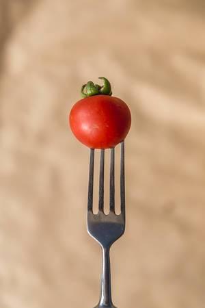 Tomato on fork. Vetical photo. (Flip 2019)