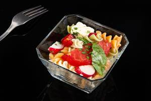 Tomato Radishes Rukola and Cheese salad above black background
