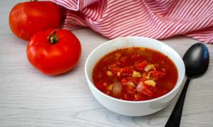 Tomato Soup in a White Bowl with tomatoes on a Side