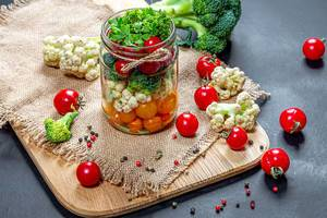 Tomatoes, cauliflower, broccoli and spices in a jar and on a table with burlap (Flip 2019)