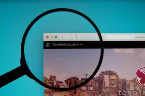 Tomorrowland website on a computer screen with a magnifying glass