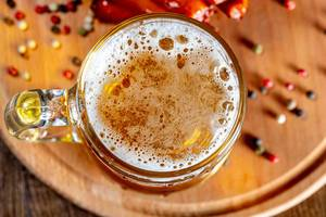 Top view a glass of beer on a wooden Board with spices