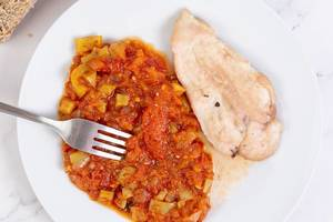 Top view above Tomato Stew with fried Chicken Breasts