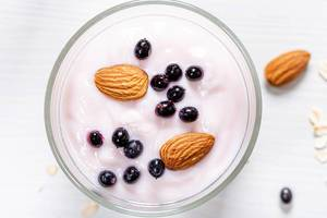 Top view black elderberry and almond nuts with yogurt on oatmeal (Flip 2019)