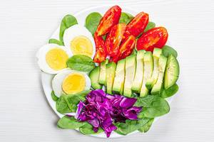 Top view boiled eggs with spinach, avocado, purple cabbage and tomatoes