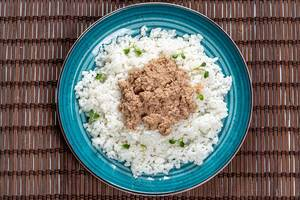 Top view boiled rice with tuna in green plate