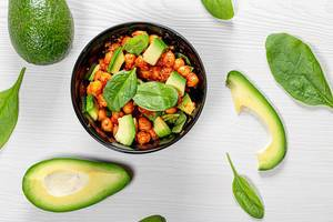 Top view chickpeas in tomato sauce with fresh avocado and spinach on white wooden background (Flip 2019)