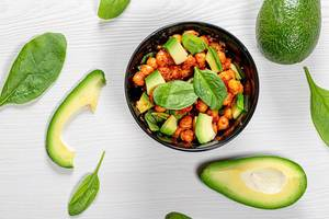 Top view chickpeas in tomato sauce with fresh avocado and spinach on white wooden background