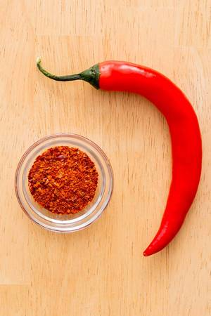 Top View Close Up Photo of Red Chili Pepper next to a small Bowl of Chili Powder on Wooden Background