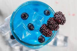 Top view, cocktail with ice cubes, mulberry and blueberry