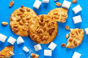 Top view, cookies with peanuts and sugar cubes on a blue background