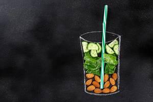 Top-view der Smoothie Zutaten Gurken, Mandel und Salat in einer Glasumrandung aus Kreide auf schwarzer Tafel. Symbolik für Gesundes-Essen mit Freiraum