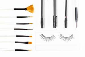Top view, different cosmetic brushes, mascara brushes and false eyelashes on a white background
